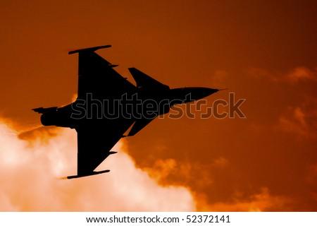 """JAS 39 Gripen"", swedish fighter aircraft on a ferruginous sky . - stock photo"