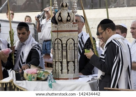 JERUSALEM-OCT. 02: The Jews in prayer at the Western Wall during Jewish holiday of Sukkot, October 2, 2012 in Jerusalem, Israel.Etrog and Lulav is two of four species used during of Sukkot. - stock photo