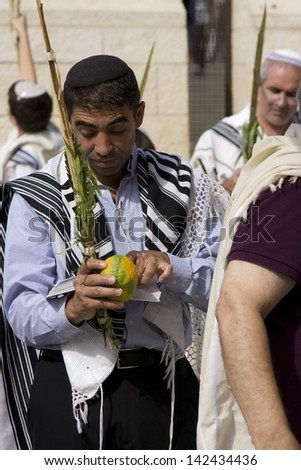 JERUSALEM-October 02: The Jews in prayer at the Western Wall during Jewish holiday of Sukkot, October 2, 2012 in Jerusalem, Israel.Etrog and Lulav is two of four species used during of Sukkot. - stock photo