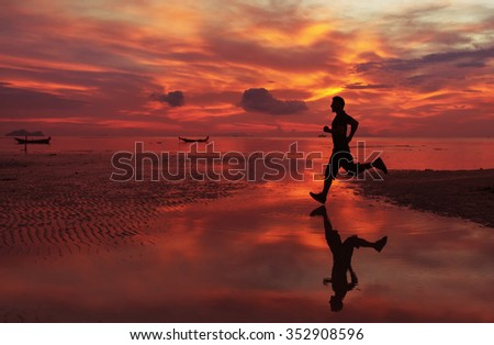 jogger on sunrise along the sand beach with mirror on the water
