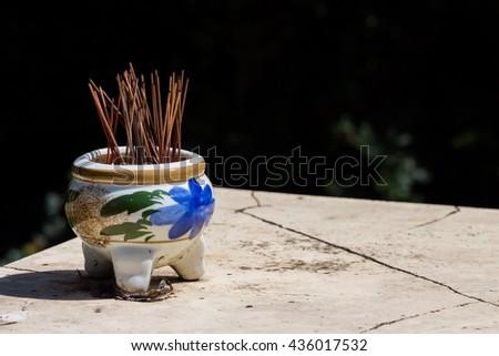 joss stick pot, incense burner on a table outside  - stock photo
