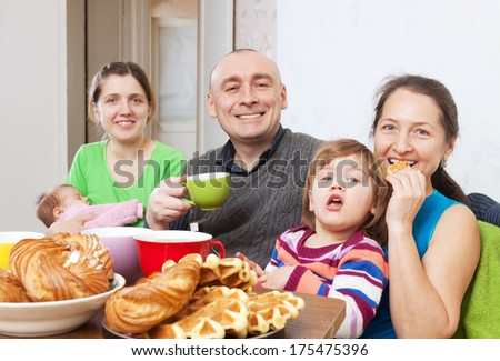 joyful  family drinks tea with baked at home