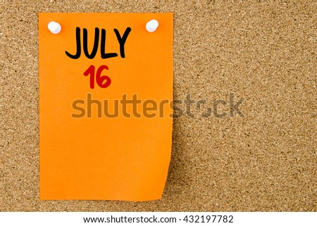 16 JULY written on orange paper note pinned on cork board with white thumbtacks, copy space available - stock photo