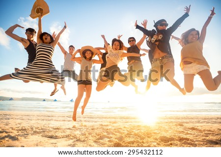 jumping at the beach, summer, holidays, vacation, happy people concept - stock photo