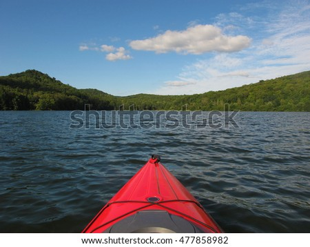 Kayaking on a lake on a beautiful summer day. There are hills in the distance.