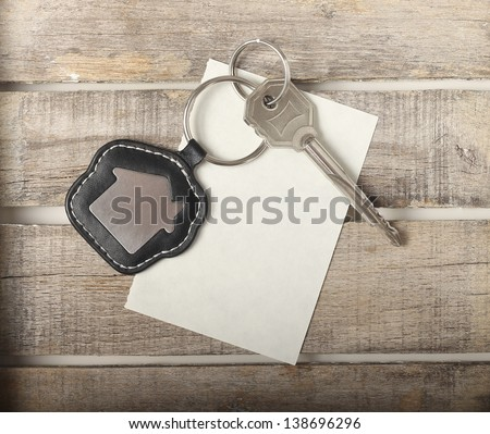 Key with house icon on wooden background - stock photo