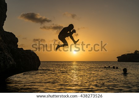 Kids cliff jumping in the sunset - Curacao views a small Caribbean Island in the Dutch Antilles