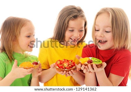 Kids eating cake with cream and fruits - stock photo