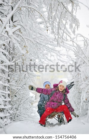 Kids sliding in winter time - stock photo