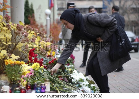 KIEV,UKRAINE - November 14, 2015: People lay flowers at the French Embassy in Kiev in memory of the victims of the November 13 terror attacks in Paris.  - stock photo