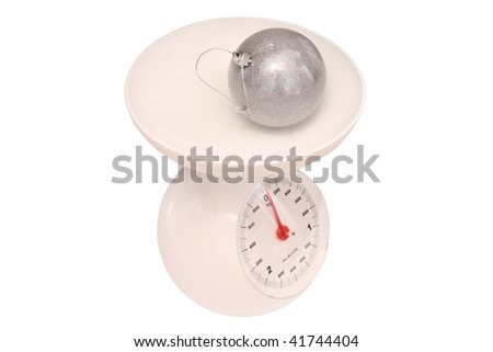 kitchen scale with Christmas-tree decoration under the white background - stock photo