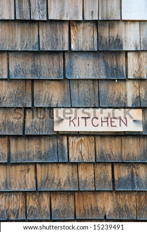 """Kitchen"" sign on shingle cabin wall - stock photo"