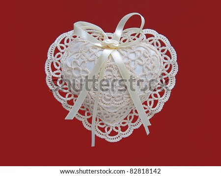 lace heart pillow on red background - stock photo