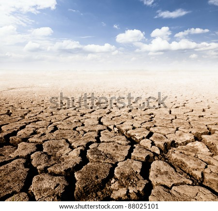 land with dry cracked ground and blue sky - stock photo