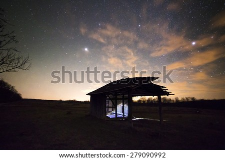 Landscape with vintage wooden shack near the forest under the stars light  - stock photo