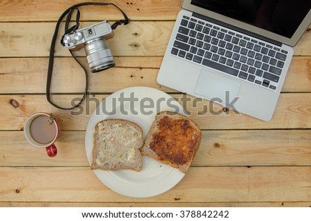 laptop, camera, coffee and  bread on wooden table. - stock photo