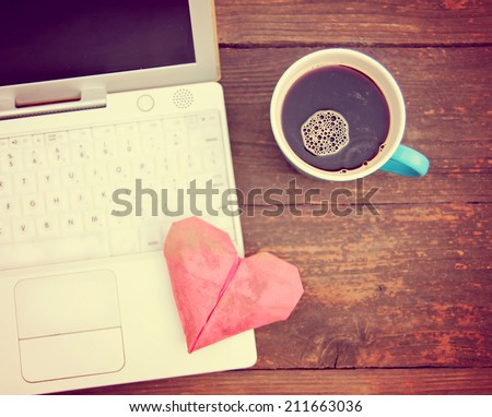 Laptop or notebook with cup of coffee and origami heart on old wooden table toned with a retro vintage instagram filter  - stock photo