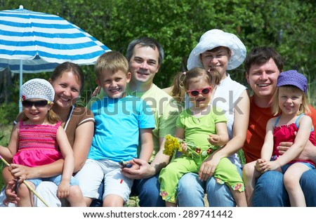 large family with children relaxing together in the park - stock photo