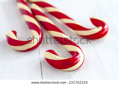 3 large red and white striped candy canes sitting on white wooden table - stock photo