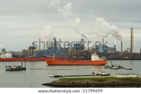 2 large ships in harbor, oil refinery in background, heavy industry pollution - stock photo