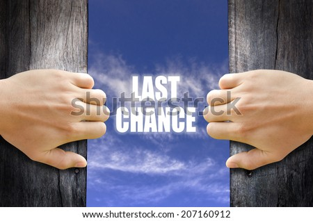 """Last Chance"" text in the sky behind 2 hands opening the wooden door. - stock photo"