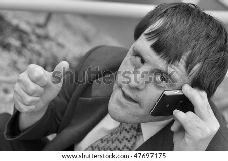 Laughing young down syndrome man enjoying a conversation over the cellphone
