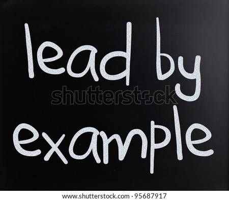 """Lead by example"" handwritten with white chalk on a blackboard - stock photo"
