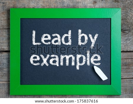 """Lead by example"" word written on green framed chalkboard on wooden background  - stock photo"