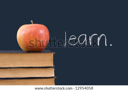 """""""learn"""" written on blackboard with apple and books - stock photo"""