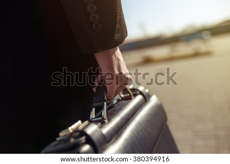 leather briefcase in his hand. young businessman walking on the street
