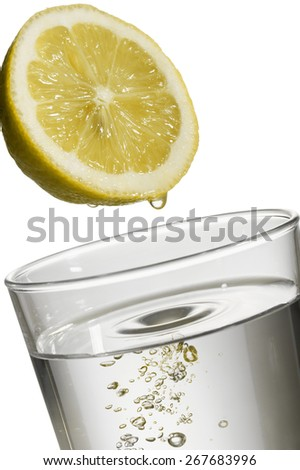 lemon drop on natural water glass, on white background - stock photo