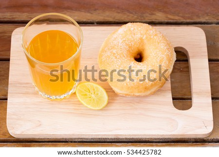 lemon tea and sweet donut on wood table.