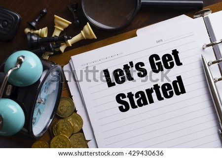 """""""Let's Get Started"""" text on notebook on a wooden table with open diary, clock, stethoscope, black and white chess, golden coin and pen - conceptual images - stock photo"""