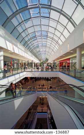 3 levels of a shopping mall with glass top. - stock photo