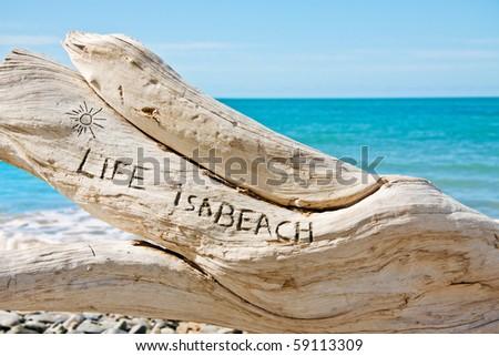 'Life is a beach' written on a log on a beautiful tropical beach - stock photo