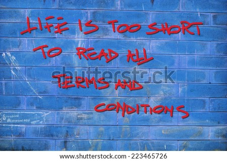 """life is too short to read all terms and conditions"" written with spray can on a blue brick wall - stock photo"