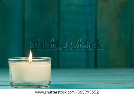 light  burning brightly candles on old wooden background. Spa, meditation, ritual, flavored. turquoise color - stock photo