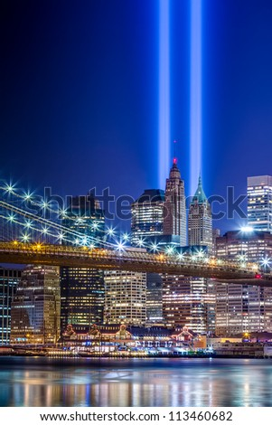 911 Lights over New York City - beautiful HDR image of September 11th commemoration beams over Brooklyn Bridge with Manhattan skyscrapers at night - stock photo