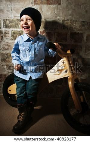 Little biker against a brick wall - stock photo