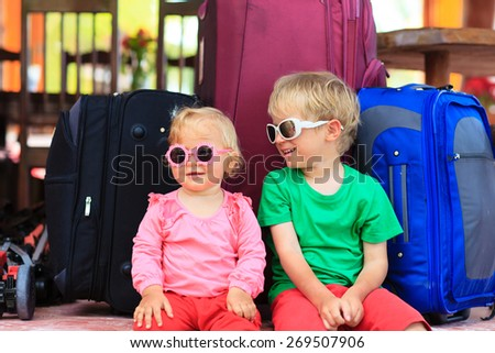 little boy and toddler girl sitting on suitcases ready to travel, kids travel concept - stock photo