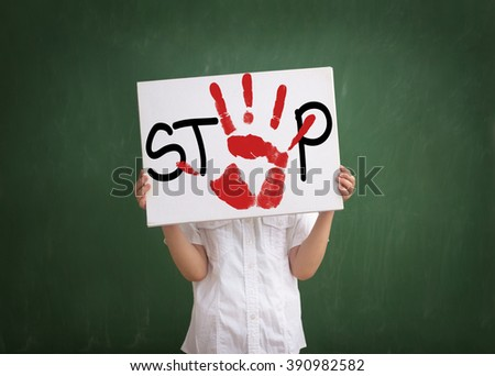 Little boy holds a table with message that bullying at school must be stopped  - stock photo