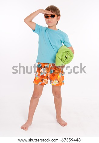 Little boy in swimming trunks with a rolled up beach towel and sunglasses - stock photo