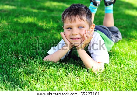 little boy laying on the sunny meadow