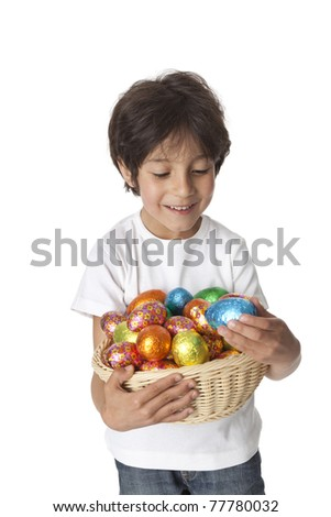 Little boy with a basket of chocolate Easter eggs on white background - stock photo