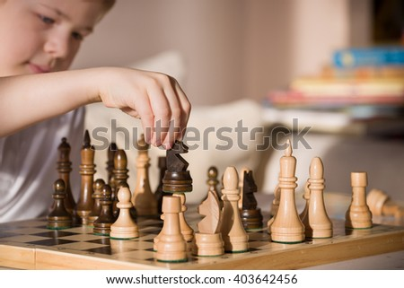 Little clever boy concentrated and thinking while playing chess at home. - stock photo