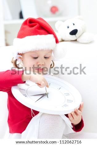little cute girl wait Christmas  big white clock - stock photo