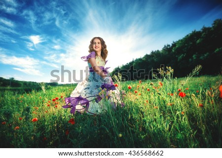 little daughter on nature in a field of poppies. Happy girl outdoors and sunset