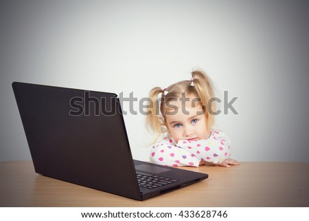 little girl at the computer. Sitting at the table. - stock photo