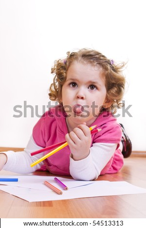 little girl drawing on the floor and  sticking out tongue - stock photo