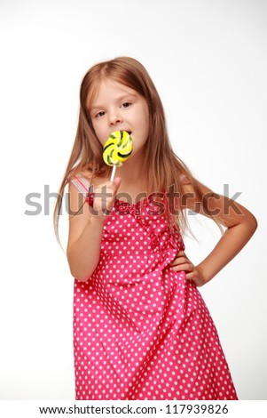 little girl holding a big round swirl lollipop on Food and drink concept theme/Lovely little girl is posing on camera with candy - stock photo